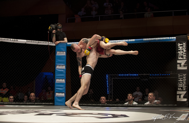 Gavin Kelly lifts Dylan Sheehan into the air before slamming him down on the mat. Cagewarriors 63, The Helix, DCU. 31st December 2013