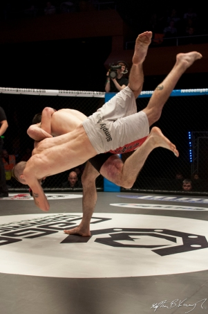 Kieran O'Brien is flipped and slammed to the mat by Mick Brennan. Cagewarriors 63, The Helix, DCU. 31st December 2013