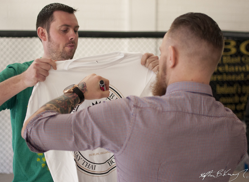 Conor Mcgregor, right, signs the Spatraten T-Shirt of Stephen Meagher at the opening of the new Straight Blast Gym branch on the Naas Road, Dublin. 11th January 2014