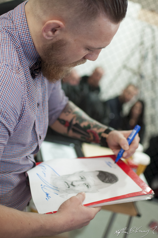 Conor McGregor signs a portrait of himself for a young fan at the opening of the new Straight Blast Gym branch on the Naas Road, Dublin. 11th January 2014