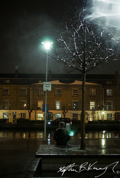 A man sits in the rain at Portobello Harbour, Dublin. 9th March 2014