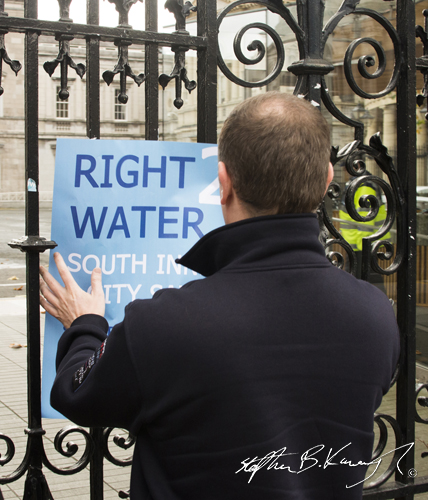 A protestor attaches his sign to the gates of Leinster House during a march against the incoming water charges in the Republic of Ireland. Kildare Street, Dublin. 1st November 2014